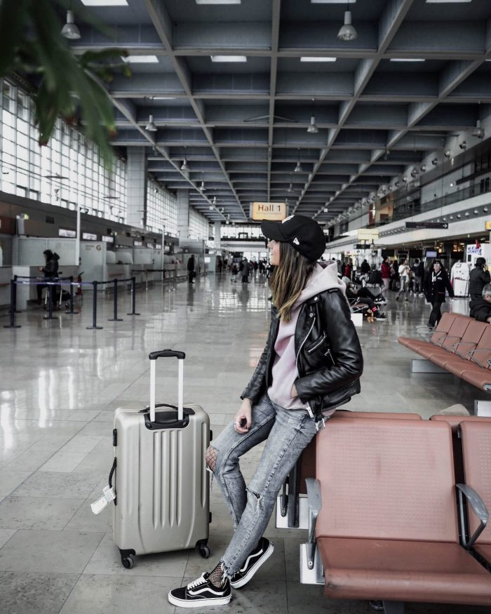 Federica L. has absolutely nailed the concept of 'travel chic'. This laid-back look, consisting of acid wash denim jeans with fishnets peeping through, a light pink hoodie and a leather jacket, makes for a gorgeous final aesthetic. Throw on a plain black cap to get that traveller look! Brands not specified.