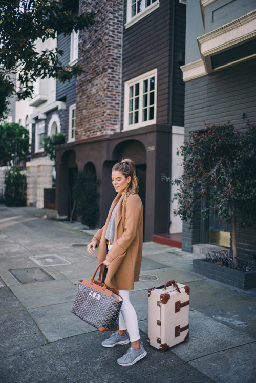 Julia Engel complements her luggage with an oversized tailored camel coat, matching belt and white jeans. Trusty pastel blue trainers and ponytail is also perfect for travel days. Coat: Vince, Sweater: Ralph Lauren, Jeans: Frame, Sneakers: Nike, Bag: Goyard, Luggage: Steamline
