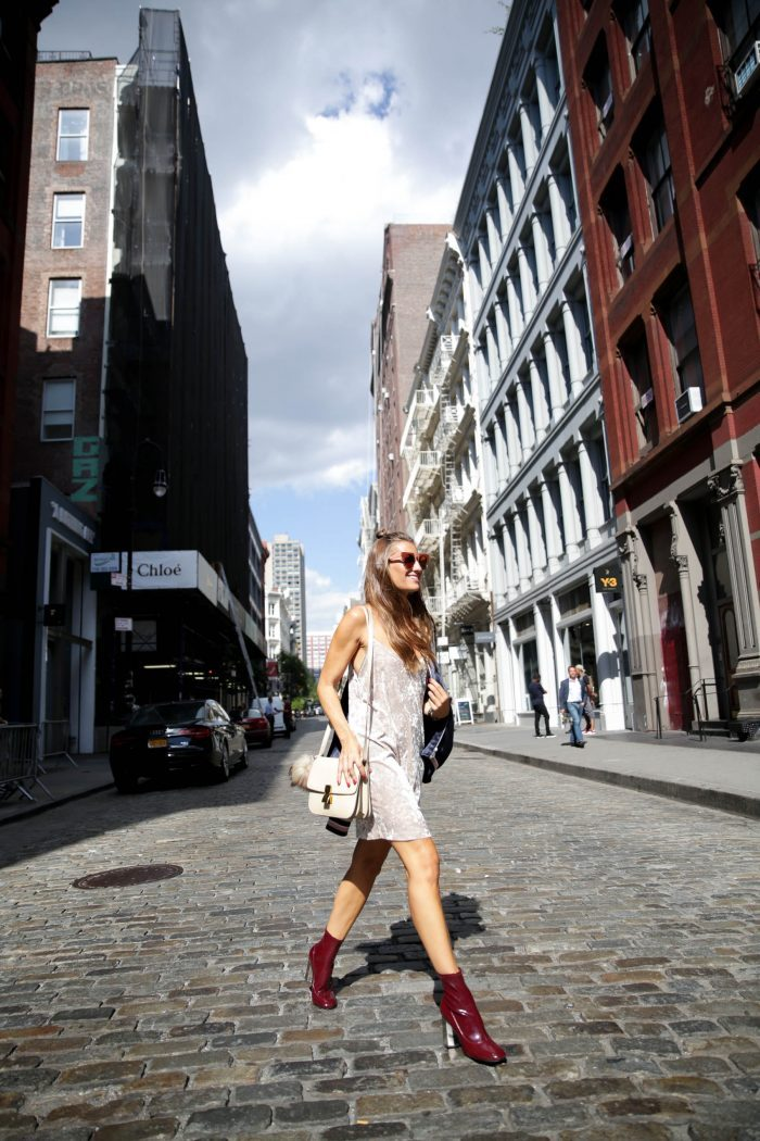 Silvia Garcia adds a pop of color to her neutral toned velvet dress by coordinating it with maroon boots. If maroon isn't your color then opt for black boots or heels for another take on this look. Dress: Zara, Bomber: H&M, Boots: Senso, Sunglasses: Marni x Optica Guia, Bag: Celine