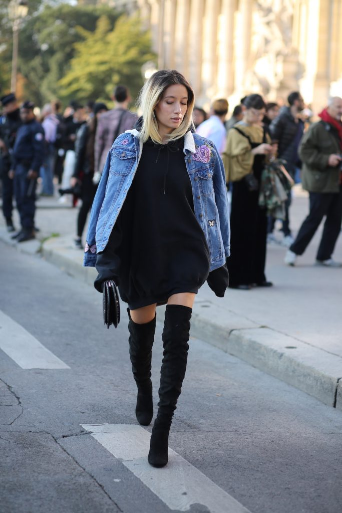 Alexandra Guerain shows how to be chic, and on trend, during pregnancy. She wears an embroidered denim jacket with roses and butterflies across the sleeves and the shoulders. This is paired with an oversized black pull dress with its extra-long sleeves, a pair of simple over-the-knee boots and a croc skin purse to complete a comfortable, yet sophisticated look.  Black pull dress, Thigh High Boots and Denim Jacket – all by New Look.
