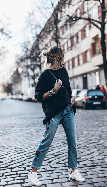 Jacqueline Mikuta wears a pair of embroidered denims with chili and rose motifs down each leg. She wears an oversized grey sweater and keeps the look casual with a pair of white sneakers. The look is accessorized with an over-the-shoulder black bag that completes this super urban look, ready in time  for Sunday Brunch.  Jeans: GRLFRND Denim via Revolve, Sweater: H&M, Shoes: Isabel Marant Etoile, Bag: Ganni.