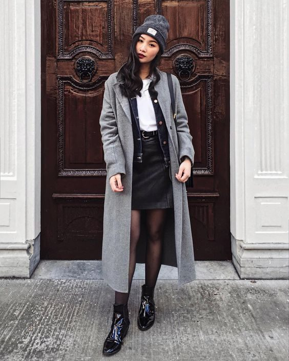Levi is sleek and sophisticated in this greyscale outfit consisting of a leather mini skirt, white tee, and doubled up jackets for an alternative take on a classic look. Grey coats are must-haves this season; get yours now for endless outfits! Brands not specified.