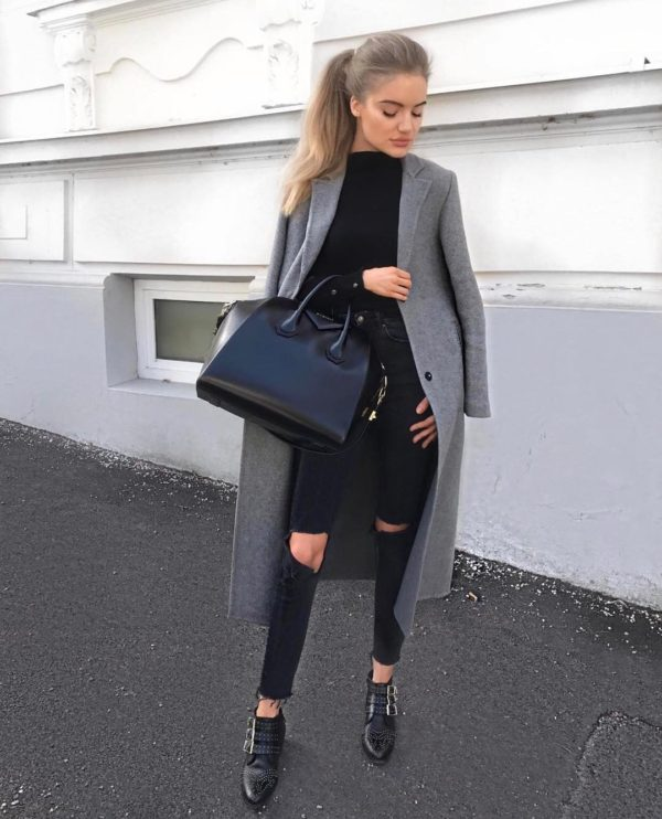 Viktoria J. Hutter wears a grey overcoat with distressed black jeans and a plain black top, creating a contrast of colours which add to the sleek chic feel of this look. Viktoria wears this style with black buckled loafers and carries a large Givenchy bag. Coat: Zara, Bag: Givenchy.