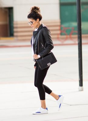 Christine Andrew is wearing aviator sunglasses, three-quarter length black leggings, a quilted black cross-body bag and white sneakers with blue accents. Jacket: AllSaints, Pants: L'Agence, Shoes: Puma, Purse: Chanel.