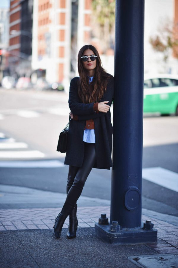 Paola Alberdi is wearing a long navy wool coat, black cross-body bag, blue button-up shirt, burnt red suede jacket and black high-heeled leather ankle booties. Coat: COS, Jacket: Sanctuary, Shirt: LXE, Leggings: LXE, Boots: Max Mara