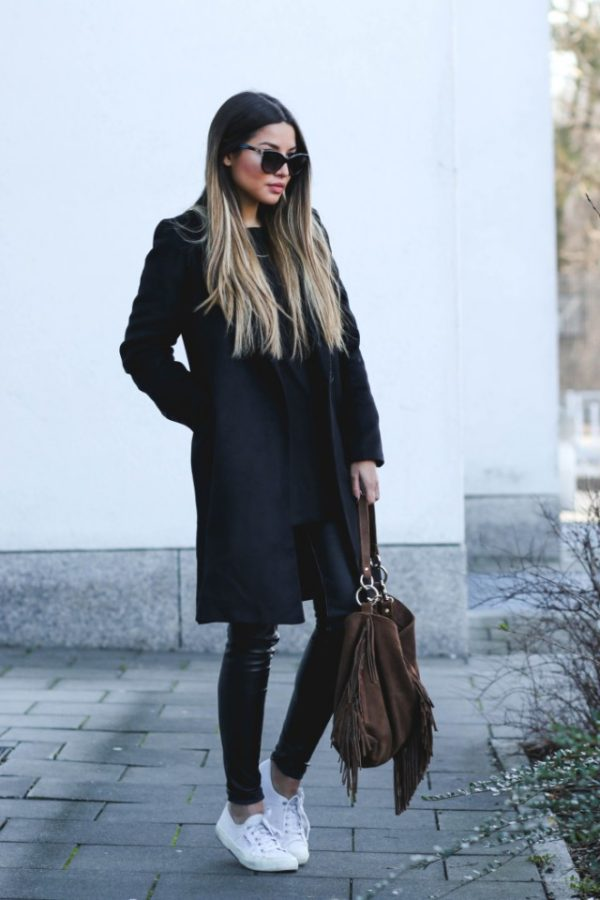 Consuelo Paloma is wearing a black trenchcoat, black leather leggings, classic white sneakers and carrying a camel suede fringe bag. Coat: Shein, Shirt: H&M, Pants: H&M, Bag: Neat.To, Sunglasses: Dolce & Gabbana, Shoes: Superga