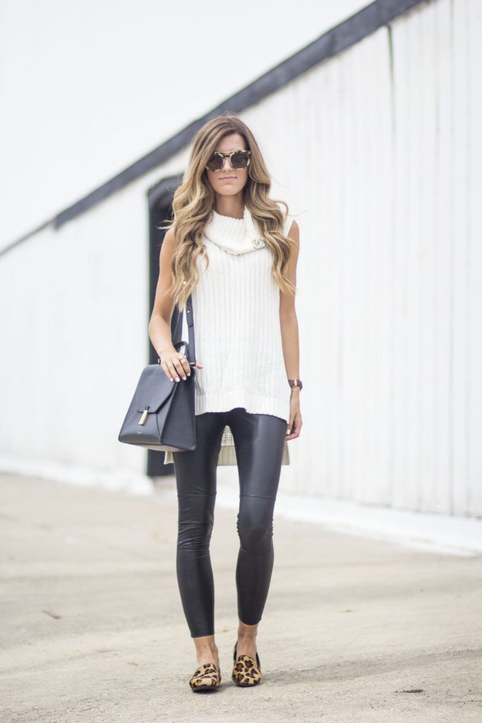 Brenna is wearing a sleeveless white cowl-neck knit sweater, cheetah print loafers, embellished black leather leggings and retro tortoise sunglasses. Sweater: Ella Moss, Leggings: Ella Moss, Sunglasses: SheIn, Bag: Ted Baker, Shoes: Aerosoles
