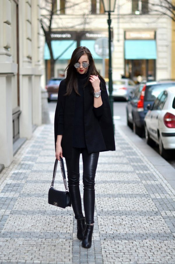 Barbora Ondrackova is wearing a black cape coat, black knit turtleneck sweater, leather leggings, studded black leather ankle boots and carrying a black quilted leather bag. Cape: Missguided, Turtleneck: Proenza Schouler, Leggings: Balenciaga, Boots: Givenchy, Bag: Chanel, Sunglasses: Dior, Watch: Michael Kors