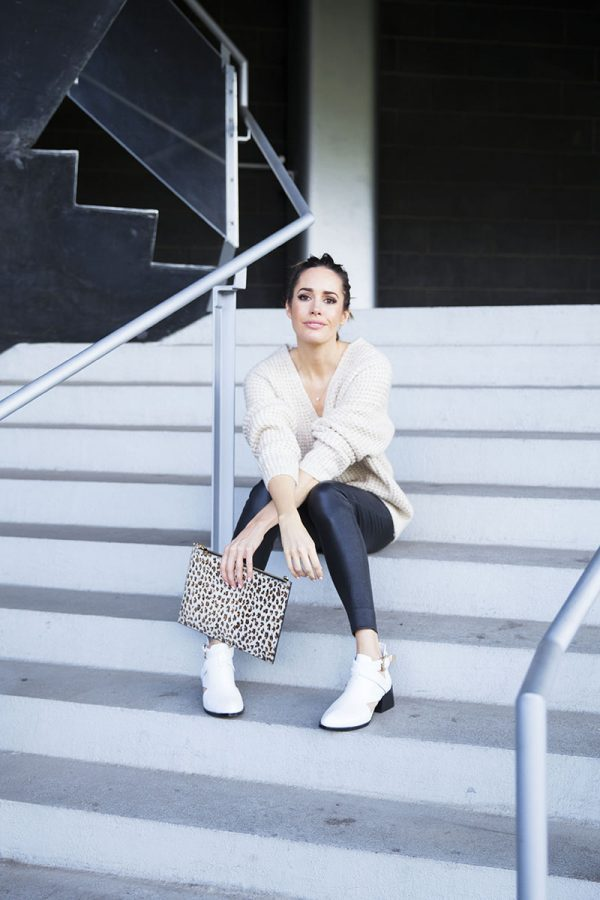 Louise Roe is wearing an oversized cream knit sweater, black leather leggings, white leather ankle boots and carrying a leopard-print clutch. Sweater: Wilfred, Pants: Ralph Lauren, Boots: Senso, Clutch: Aspinal of London
