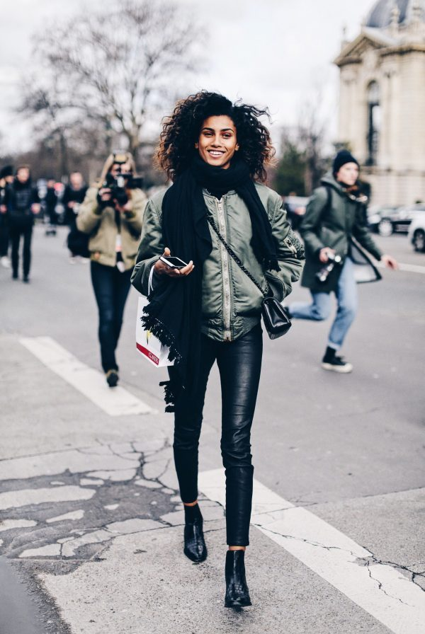 This look photographed by Clochet features a military green bomber jacket, oversized black fringed scarf, a black cross-body bag and pointed-toe black leather ankle boots. Brands: Unspecified.