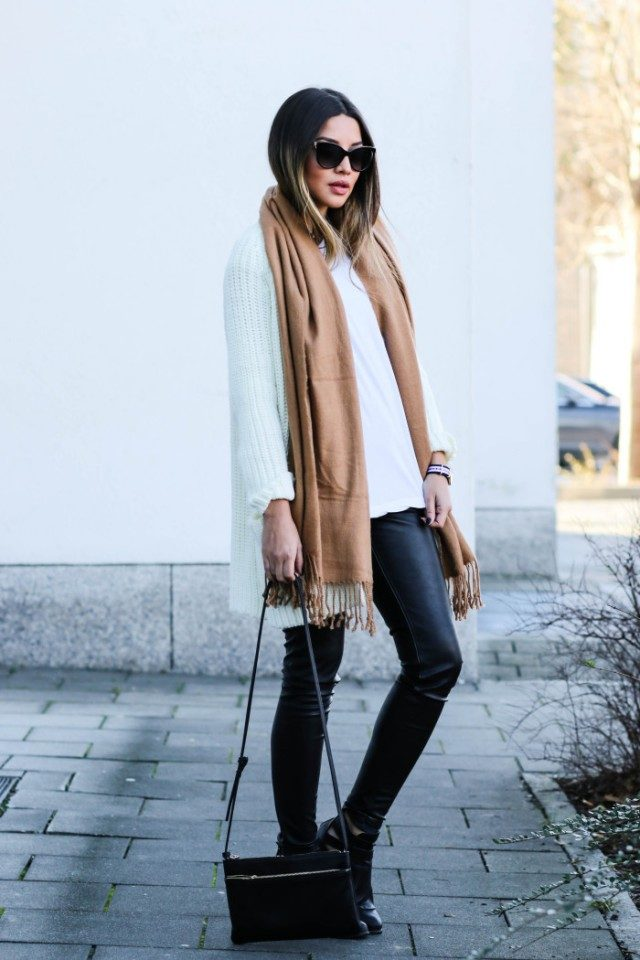 Consuelo Paloma is wearing an oversized white knit cardigan, a camel fringed scarf, black leather pants, black leather ankle boots and carrying a black leather zipped crossbody bag. Cardigan: H&M, Scarf: H&M, Shirt: Asos, Pants: H&M, Boots: Boohoo, Bag: Mango, Sunglasses: D&G