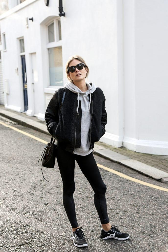 Lucy Williams is wearing quilted black leggings, a black Sherpa bomber jacket, black and white sneakers, a grey cotton hoodie and carrying a black fringed leather satchel. Shoes: Nike: Leggings: Nike, Hoodie: TopShop, Jacket: Mother, Bag: Mansur Gavriel