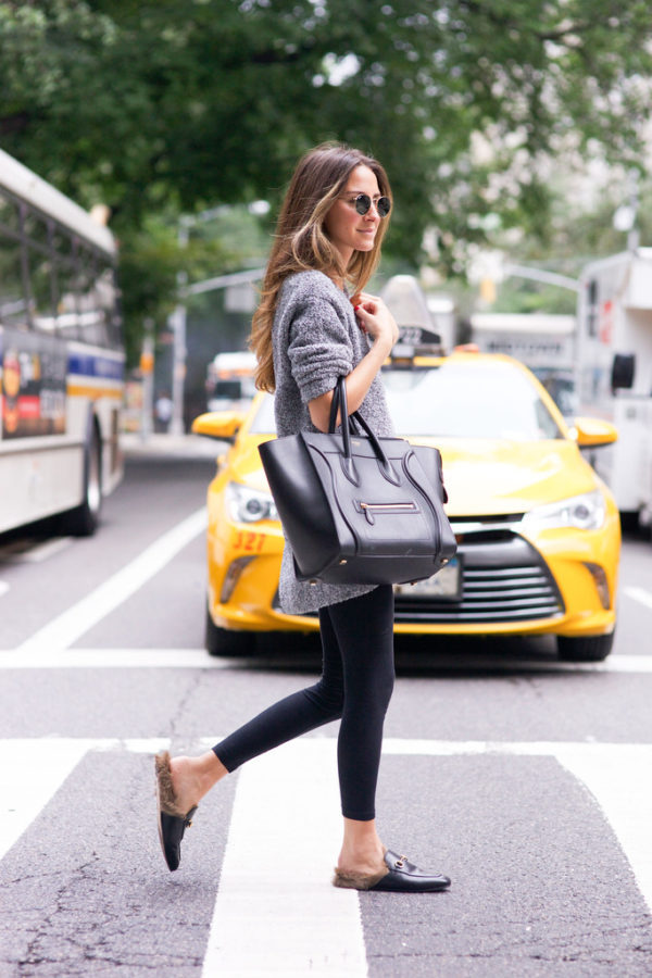 Arielle Nachami is wearing a chunky grey knit sweater, black leggings, retro sunglasses, leather and fur loafers and carrying a black leather tote. Leggings: Solow, Sweater: NastyGal, Shoes: Gucci, Bag: Celine. Sunglasses: Ray Ban