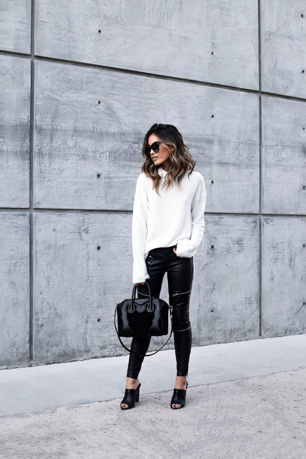 Jill Wallace is wearing embellished black leather moto leggings, a creamy white turtleneck sweater, and a black leather and suede purse with open-toed black pumps. Sweater: Blue Planet, Pants: Zara, Shoes: Tony Branco