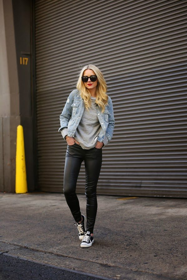 Blair Eadie is wearing a stone-washed jean jacket, classic black Converse, and a distressed grey cotton sweatshirt. Jacket: Mason, Leggings: Current/Elliott, Shoes: Converse, Bag: Mansur Gavriel, Denim Jacket: Marc Jacobs, Sweatshirt: Robert Rodriguez, Sunglasses: Karen Walker