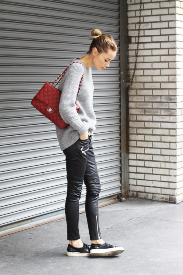 Anine Bing is wearing a knit grey sweater, leather leggings embellished with zippers, black patent leather sneakers and red quilted cross-body bag. Everything except bag: Anine Bing, Bag: Chanel