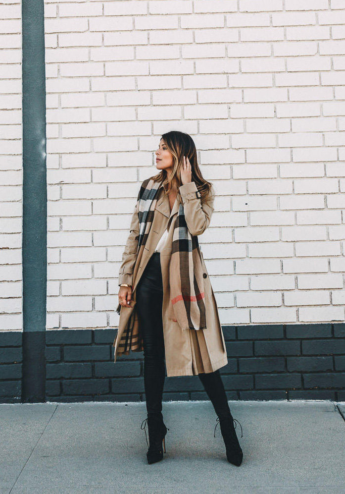 Pam Hetlinger is wearing a khaki trenchcoat, classic plaid scarf, high-waisted tight black leather leggings and black lace-up booties. Coat and scarf: Burberry