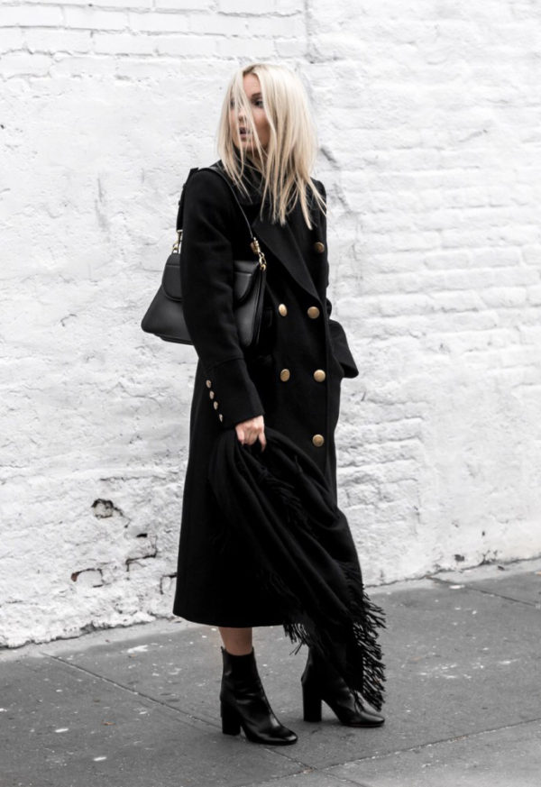 Figtny is seen in head to toe all black, wearing heeled patent leather boots, a military style maxi coat with gold button detailing, and a leather bag to match. Pair this look with an oversized scarf to capture this style!  Coat: Marks & Spencer, Boots/Scarf: Moda Operandi, Bag: J.W Anderson.