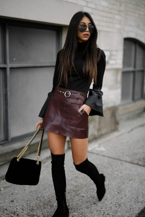 Kayla Seah is seen in a burgundy leather mini skirt, worn with a bell sleeved black turtleneck, a pair of over the knee boots, and a pair of wide rimmed shades. Skirt: Storets, Shirt: Staud, Boots: Sigerson Morrison, Bag: Gucci.