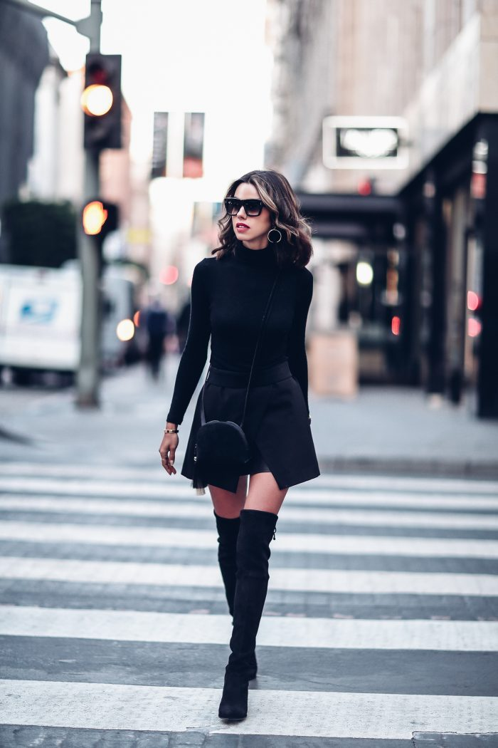 Annabelle Fleur wears a slitted A line mini skirt with thigh high boots and a simple black turtleneck to create this monochrome street style. She wears this look with a circular cross body bag, silver hoop earrings and shades. Outfit: Nordstrom.