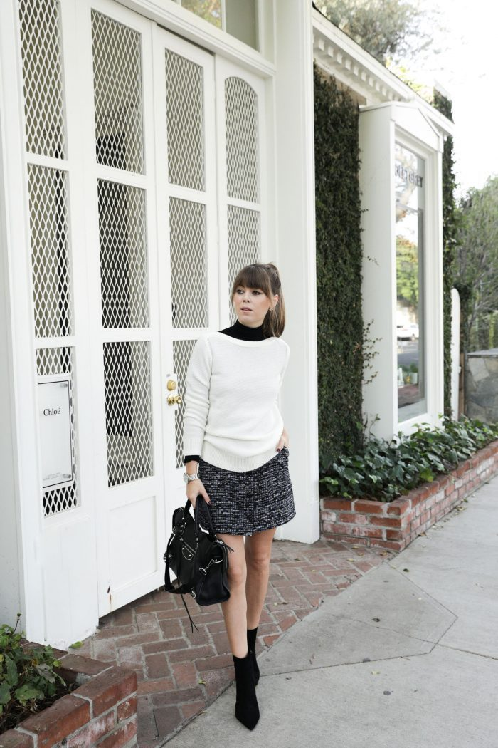 Tweed mini skirts are a winner this season! Jenny Bernheim is wearing a greyscale skirt with a layered black turtleneck and white sweater. She wears this with suede black ankle boots and a leather satchel bag. Skirt/Sweater/Boots: Banana Republic.