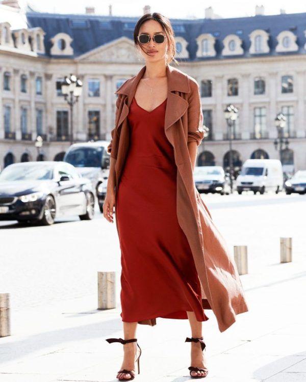 Nicole Warne combines a gorgeous scarlet slip dress with a light brown drape coat, burgundy heels, and sunglasses to create an elegant look. Dress: KITX, Sandals: Alexander Birman.