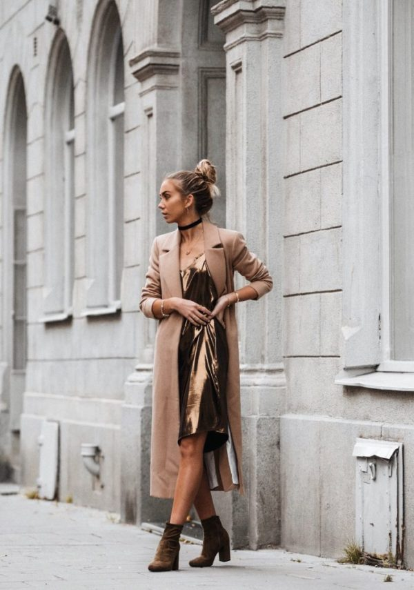 Pairing a metallic bronze slip dress with a beige three quarter length overcoat, Lisa Olsson creates a glamorous street style. She combines these pieces with brown suede boots and a simple black choker. Coat/Dress/Shoes: River Island. Choker, ASOS.