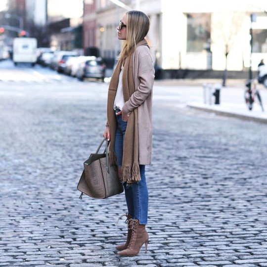 67f3f6a9c0 Helena Glazer is casually styled in a pair of classic denim skinny jeans,  spike heeled suede boots, a beige oversized cardigan, and a scarf to match.