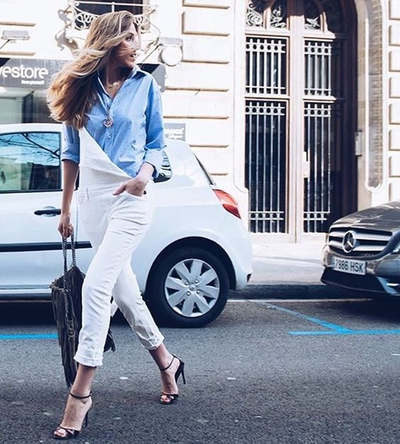 Carla Hinojosa is wearing a pair of spring white dungarees, paired with an open sky blue shirt for a tomboy style we adore. Carla wears this look with stilettos, adding endless glamour to the aesthetic. Brands not specified.