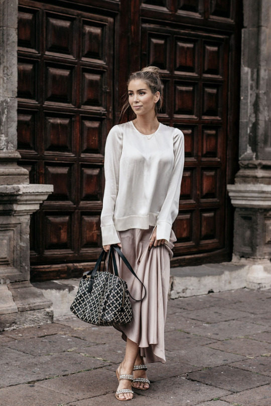 Emilie Tommerberg is wearing a relaxed oversized grey silk blouse, paired with a blush silk midi skirt and chain sandals. Top: FWSS, Skirt: Asos, Sandals: Dune