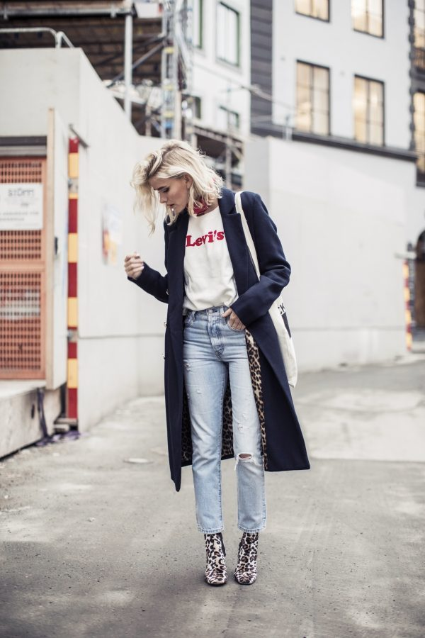 Elsa Edman is wearing a casual white cotton t-shirt, a tailored navy coat, light wash denim jeans and leopard print booties, accessorized with a red scarf and a canvas tote bag. Scarf, Sweater & Jeans: Levi's, Coat/Boots: River Island