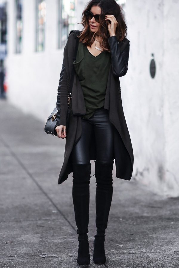 Erica Hoida is wearing a free flowing draped black cardigan, a green jersey t-shirt, black leather pants and black suede over the knee boots. Cardigan: Yigal Azrouel, Shirt: Bobi Leather, Pants: Helmut Lang, Boots: Stuart Weitzman, Bag: LYA LYA, Necklaces: Geoffrey Scott, Parpala Jewlery