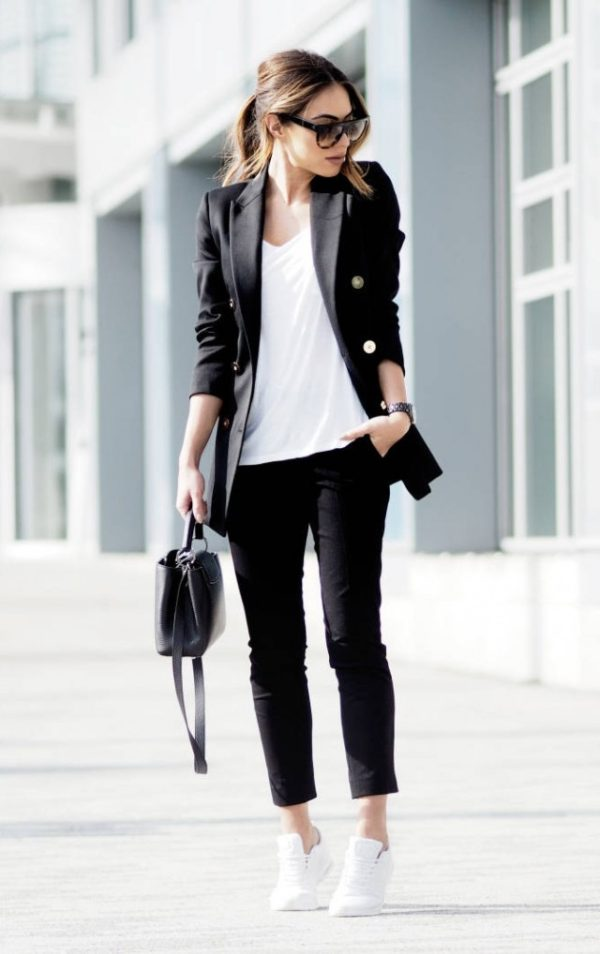 Lydia Elise Millen is wearing a black double breasted blazer, a loose white t-shirt, cropped black tailored trousers and white leather trainers. Trousers: Joseph, Blazer: Reiss, Bag: Louis Vuitton, Trainers: Nike, Tee: Missguided.
