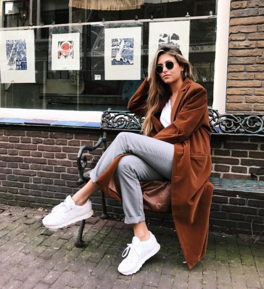 Noa Ismay de Vries wears a casual Spring outfit consisting of a full length velvet coat, worn over a white tee with grey slacks and white sneakers. She adds sunglasses to give the look that edgy feel. Trainers: Reebok.
