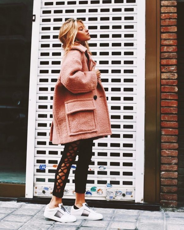 Andrea Belver is wearing a pink bouclé jacket, cropped black pants with side detail, and white trainers with black stripe detail. Pants: Laia, Shoes: Musee and Cloud