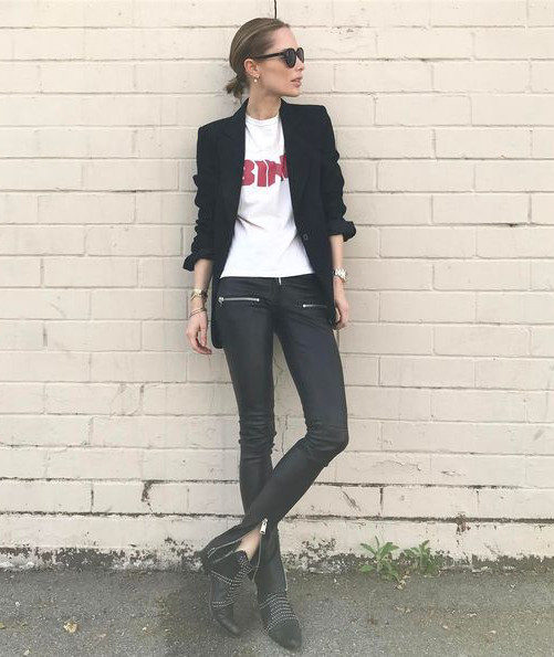 Anine Bing throws on a classic black blazer over a graphic tee to create this charmingly boyish spring style. Anine wears this with leather leggings with zip detailing and matching leather boots. Brands not specified.