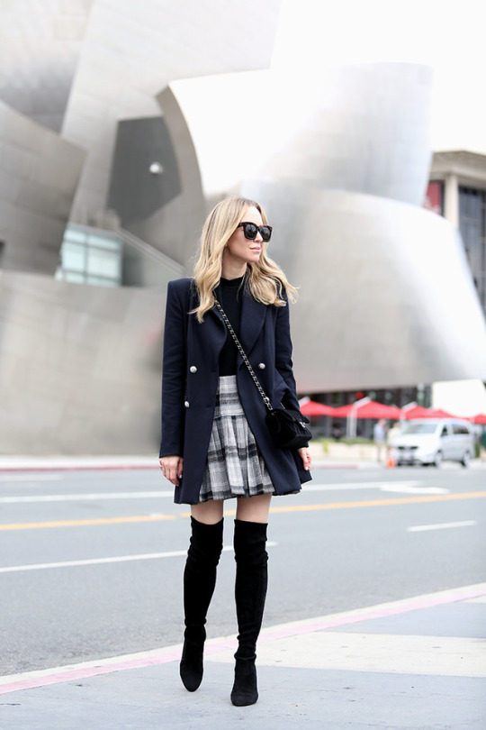 Helena Glazer is wearing a navy pea coat, a black mock neck bodysuit, a black and white tartan pleated skirt and black over the knee suede boots. Jacket: Zara, Bodysuit: Only Hearts, Skirt: ASOS, Boots: Stuart Weizman, Bag: Chanel