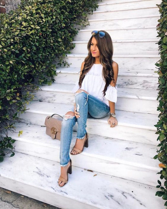 Caitlin's spring outfit consists of ripped denim skinny jeans, worn with a shoulderless white blouse and stilettos for a glamorous everyday style. Brands not specified.