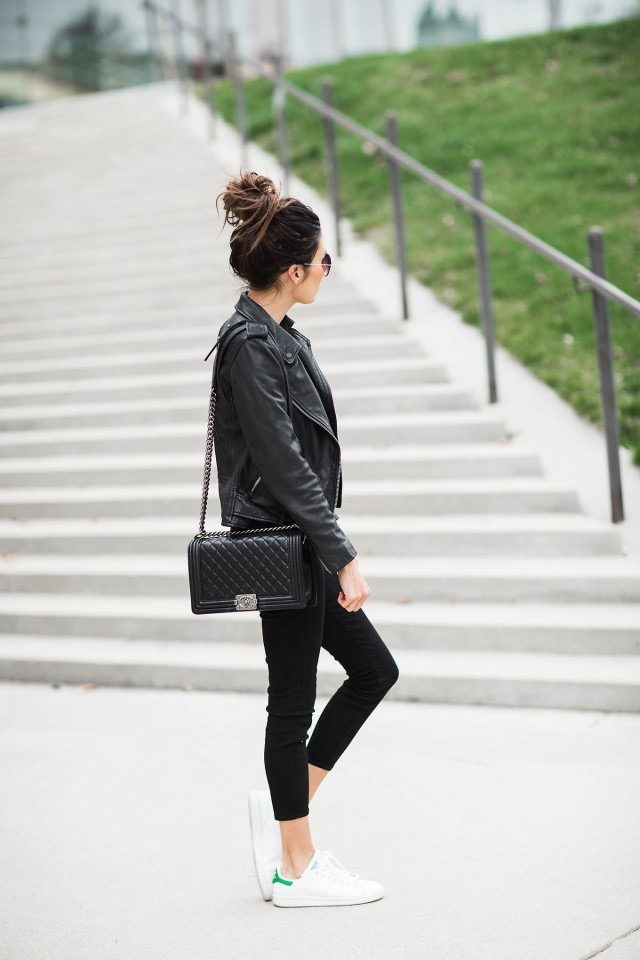 Christine Andrew is wearing a black biker leather jacket, black cropped skinny jeans, classic white leather trainers and a black quilted Chanel bag. Jacket: All Saints, Jeans: Nordstrom, Top: Ily, Trainers: Adidas, Bag: Chanel