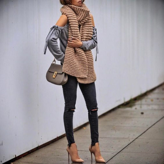 Sasha Simon is rocking a must-have Spring outfit, in distressed skinnies, nude stilettos, and a matching cable knit scarf, worn over a bow-detailed shoulderless long sleeved top. Scarf: I Love Mr Mittens.