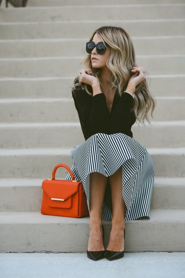 Cara Loren Van Brocklin is wearing a black wrap top, a black and white striped flared midi skirt and black leather pointed pumps. Skirt: Windsor, Top: Shopbop, Shoes: The Cammeo