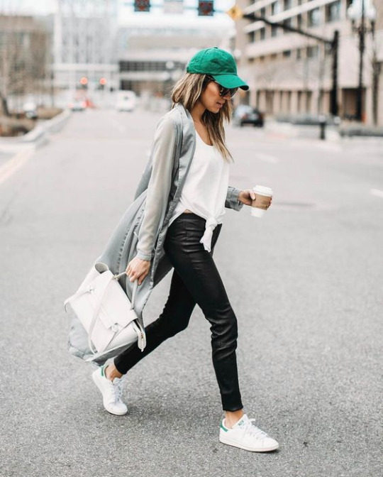 Christine Andrew's causal spring outfit consists of leather pants, a tie-front white vest, long 'boyfriend' style cardigan, and Adidas original Stan Smith sneakers. Brands not specified.
