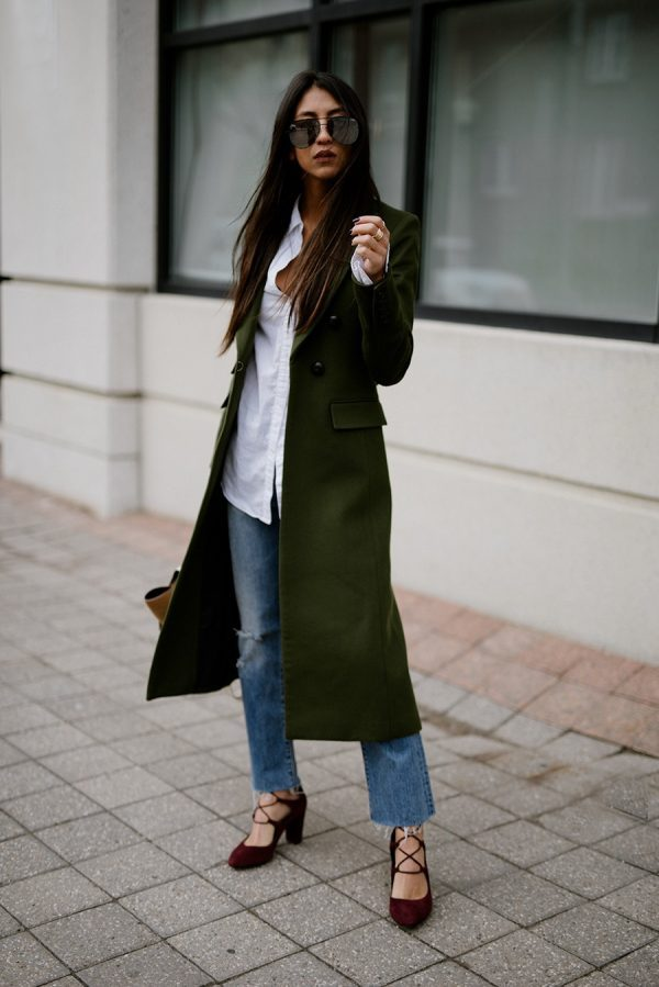 Kayla Seah is wearing a long green double breasted coat, an oversized white button up shirt, relaxed fit jeans with frayed hems and red lace up shoes with oversized aviator sunglasses.