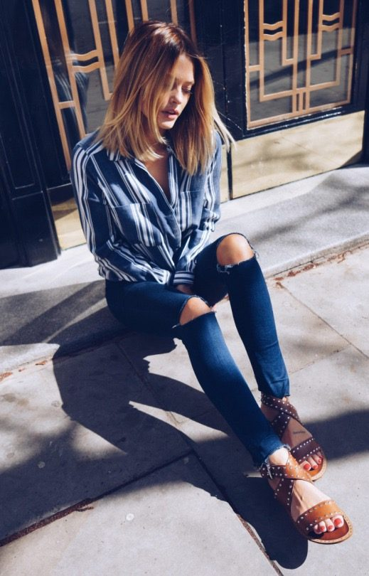 Caroline Receveur is wearing a long sleeved striped navy wrap blouse, dark wash denim jeans with torn knees, and studded tan leather sandals. Shirt: River Island, Sandals: Dune