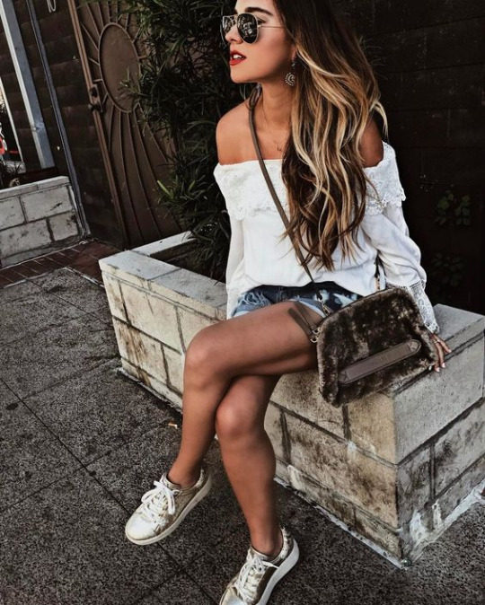 Gina Ybarra is seen in a shoulderless white blouse, worn with ripped denim cut-offs, creating a perfectly playful spring outfit. She wears this look with metallic sneakers and a rustic style cross body bag. Brands not specified.