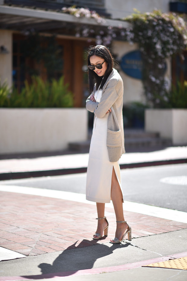 Ann Taylor is wearing a long nude cardigan, a white silk button up shirt, a white midi pencil skirt with split sides, and leather heeled sandals. Cardigan: Banana Republic, Top: Theory, Skirt: Lafayette148, Purse: Fendi, Heels: Manolo Blahnik.