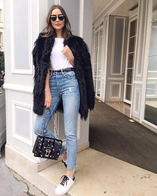 Olivia Culpo is rocking this black faux fur coat, combining it with high waisted denim jeans and retro white and black sneakers for a chic spring style. She carries a studded leather handbag and finishes the look with classic shades. Coat: RTA Brand, Jeans: Girflriend Denim, Shoes: Tony Bianco.