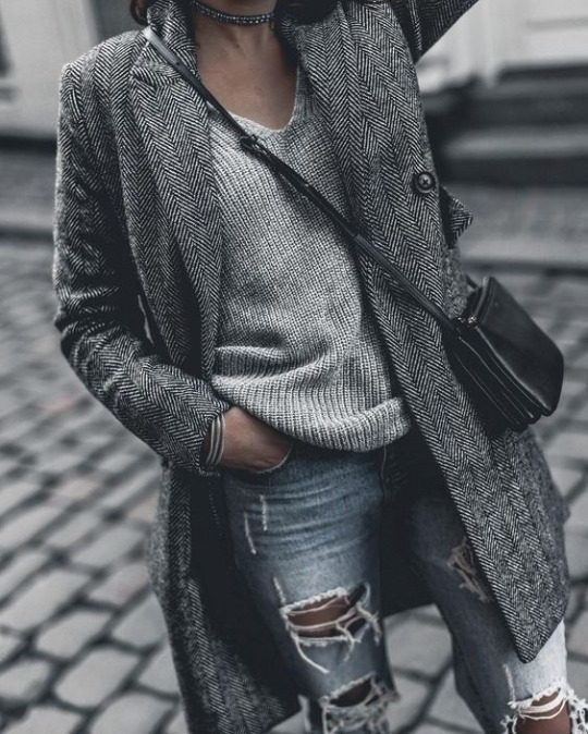 Monja W is in a grey overcoat, over a gorgeous knitted V neck and heavily ripped denim jeans. She wears this look with a glittery choker and a leather handbag. Coat: Superdry.