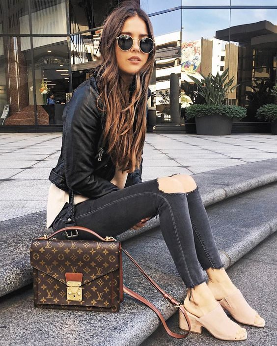 Paola Alberdi is wearing black skinny jeans here, ripped at the knee for that classic edge we all crave. She pairs these with a leather jacket and light clog style sandals for an authentic, spring style. Bag: Louis Vuitton.