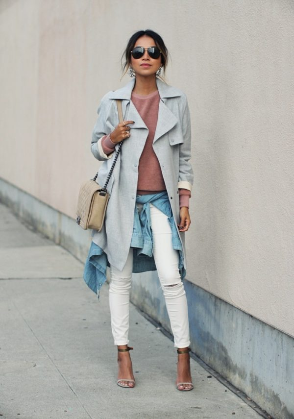 Julie Sarinana is wearing a grey trench coat, a heather pink sweater, white skinny jeans and scrappy sandals, with a blue denim jacket tied around her waist. Sweater/Coat/Jeans/Shirt: Topshop, Shoes: Isabel Marant.